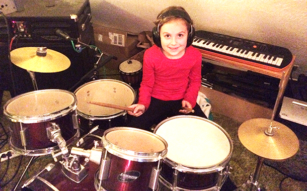 Cali, 6, playing drums