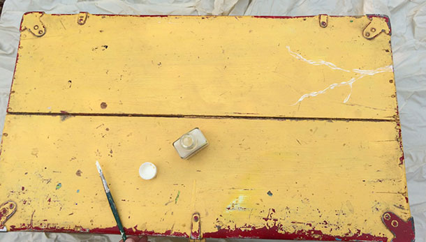 BEFORE image of Vintage footlocker. Here's where I am painting on the rubber resist to preserve the beat-up yellow paint.